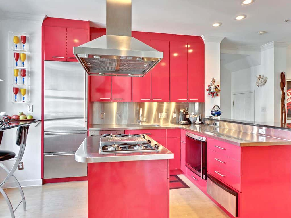A range hood hangs over a breakfast island fitted with a cooktop in this pink kitchen. It features coral pink cabinetry with stainless steel countertop and backsplash.
