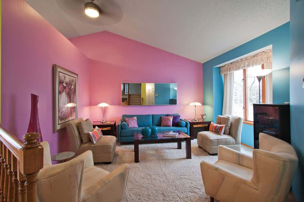 Blue and pink walls harmoniously blend into a gorgeous living room. It includes a blue couch surrounded with beige chairs over carpeted flooring.