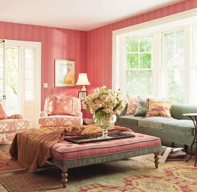 Pink living room with striped walls and a huge tufted ottoman accented with a brown throw blanket in the middle that serves as a center table and an extended sofa at the same time.
