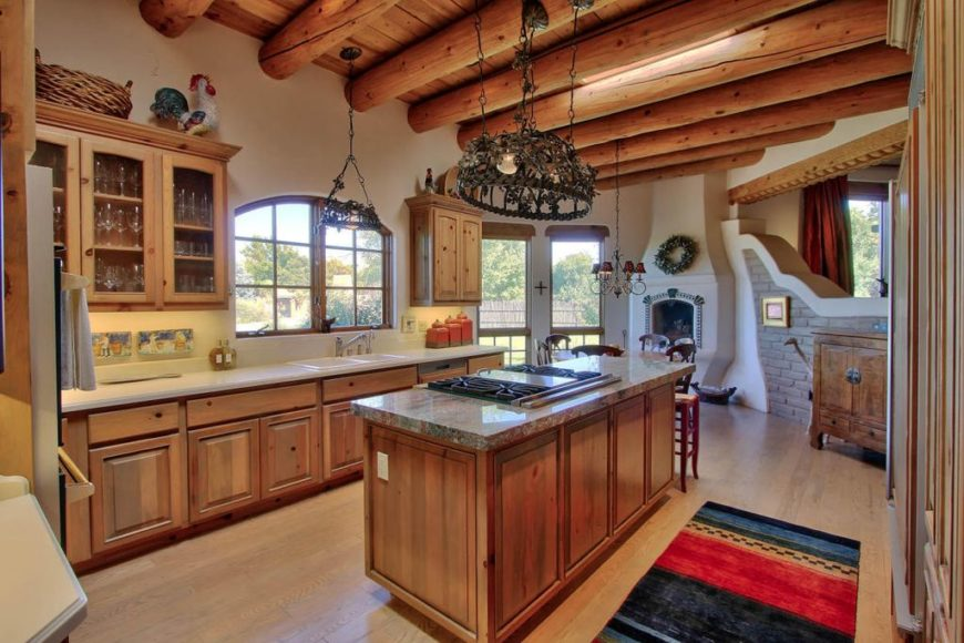 Unique wrought iron chandeliers hung from an exposed wood beam ceiling in this southwestern kitchen. It has a breakfast island fitted with a built-in cooktop.