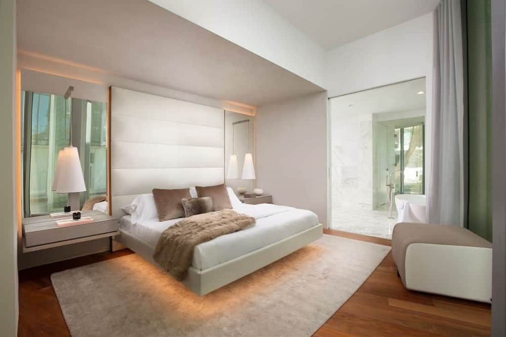 This is the primary bedroom that has a white built-in platform bed with modern lighting underneath and built-in floating bedside tables with lamps and mirrors. These are then complemented by the large cushioned headboard.