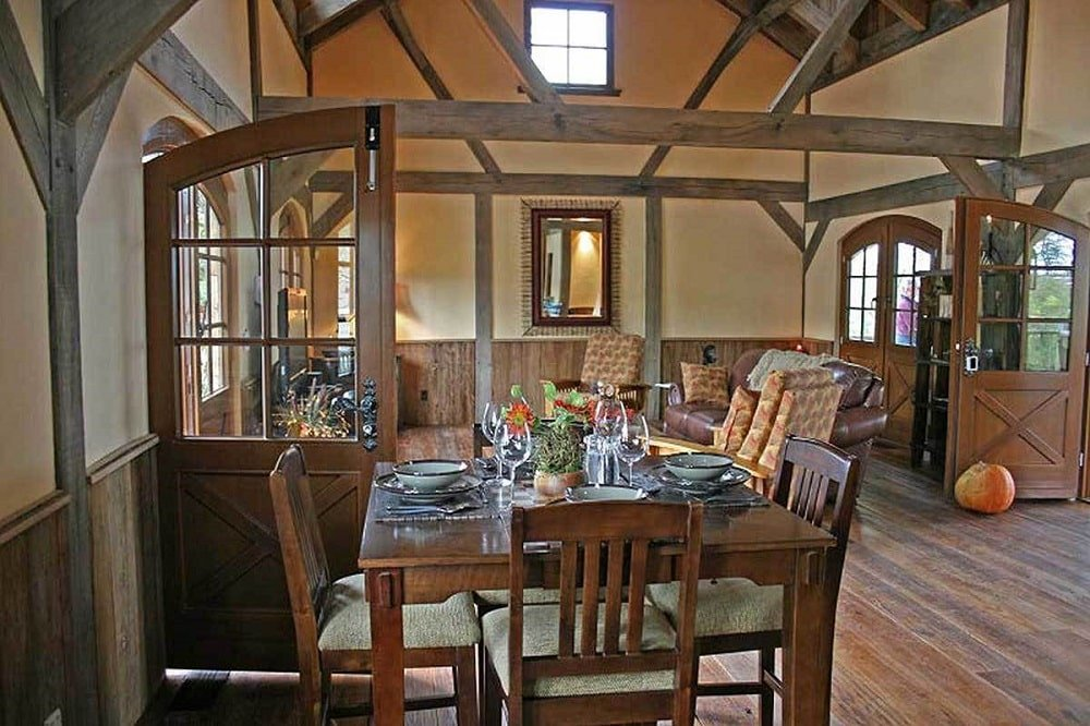 This is a view of the house interior that features the dining area with dark wooden dining set topped with a tall beamed ceiling.