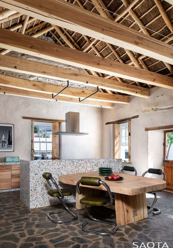 This is a full view of the eat-in kitchen with a large stone kitchen island that has an attached wooden table that matches the large wooden beams of the cathedral ceiling.