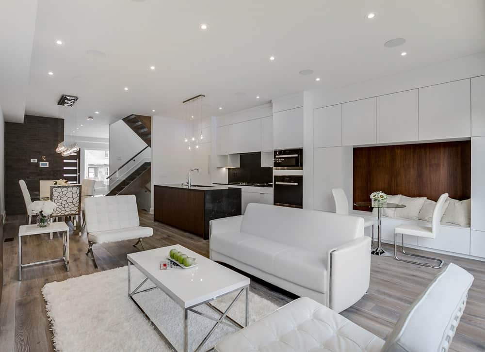 This is a view of the kitchen on the side of the living room area and an informal dining area that has a simple dining set on the side of the white cabinetry of the kitchen that has an alcove built-in bench that matches the tone of the kitchen island.