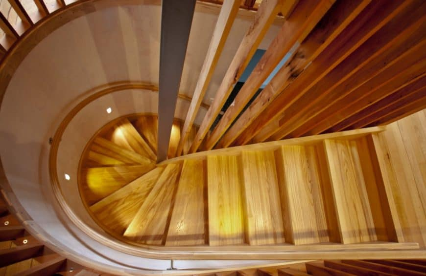 Top view of an elegant wood staircase with curved inner stringer and recycled rimu balustrade.