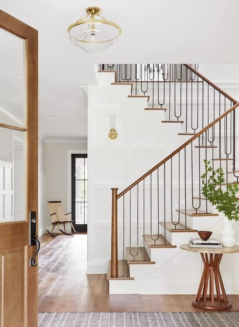 Gorgeous staircase accented with wrought iron spindles and a brass handrail. It has wood treads complementing the floor along with white wainscoted walls.
