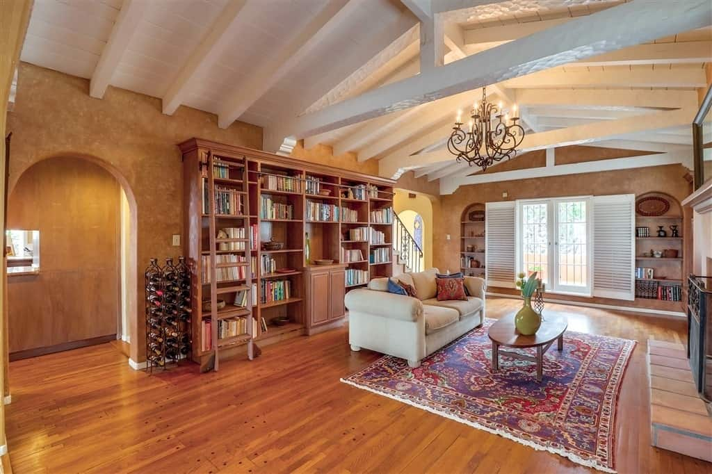 Warm living room illuminated by a wrought iron chandelier that hung from a vaulted ceiling with exposed beams. It includes an iron metal wine rack that sits beside the wooden bookshelves behind a cream loveseat.