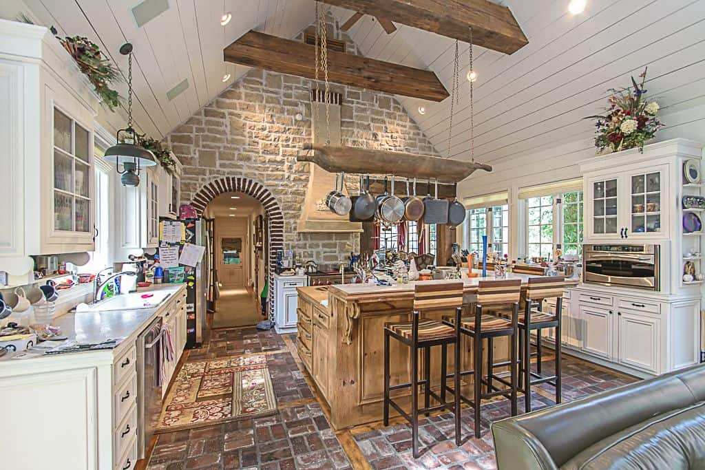Rustic kitchen showcases a stone brick accent wall and flooring. It has a white shiplap cathedral ceiling with exposed wood beams.