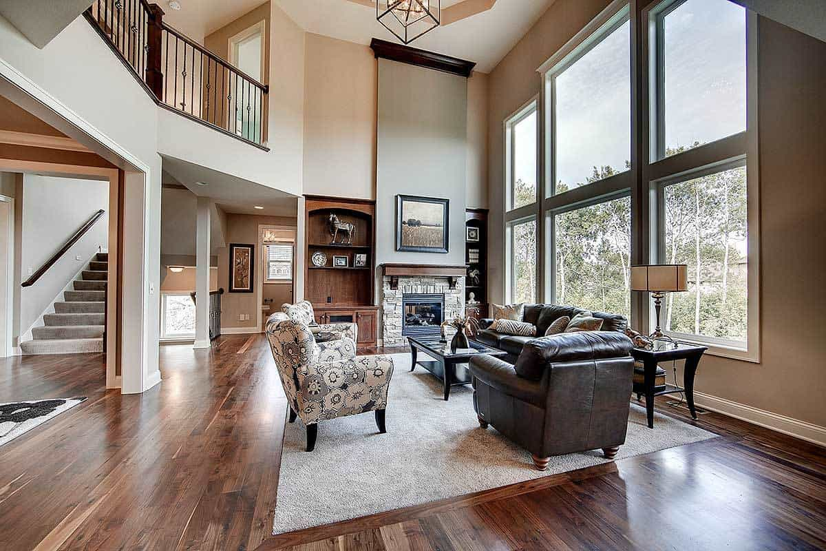 This is a spacious and airy living room with a tall ceiling paired with a large glass wall. This brings in natural lighting for the dark leather sofa set and the dark hardwood flooring warmed by the large stone fireplace on the far end.