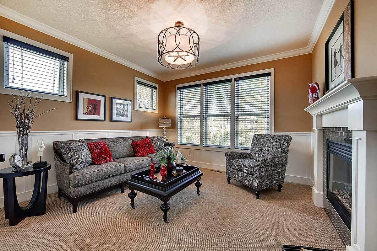 This is a cozy and intimate living room with a carpeted flooring that matches the earthy beige walls above the wainscoting. This is then contrasted by the sofa set and black coffee table across from the fireplace.