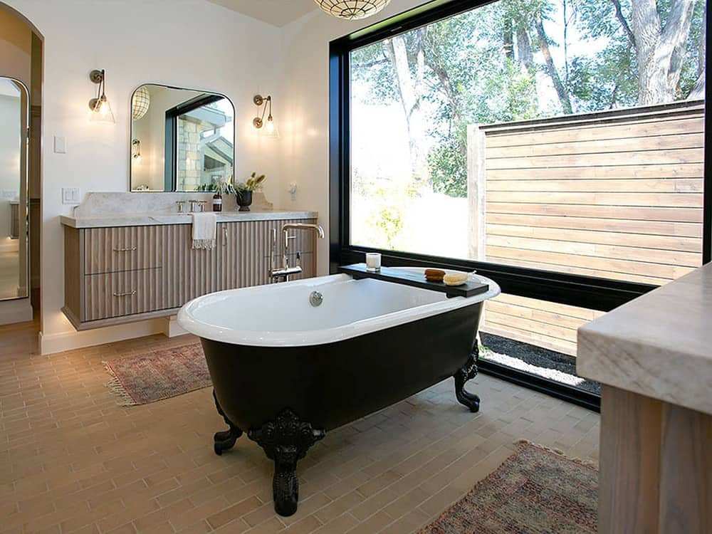 This primary bathroom has a black freestanding bathtub standing in the middle of the two floating vanities with a wooden slat facade. This bathtub is placed beside a large wall of glass that presents a nice scenic view outside as well as provide natural lighting.