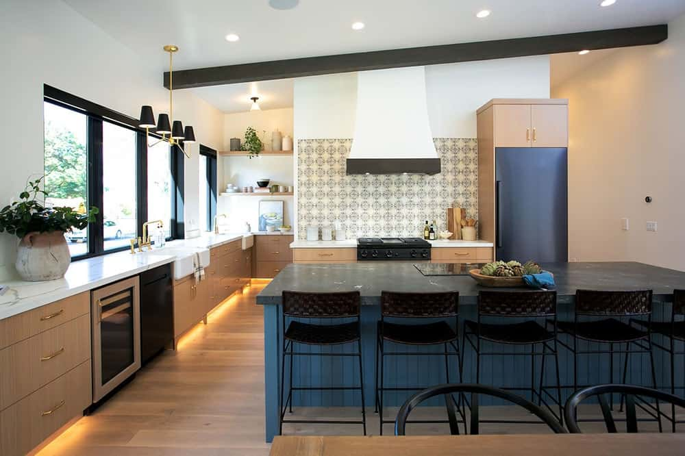 Contrasting black and white marble countertops add a striking elegance to this contemporary kitchen. It includes a decorative tile backsplash and a shed ceiling lined with a dark wood beam.