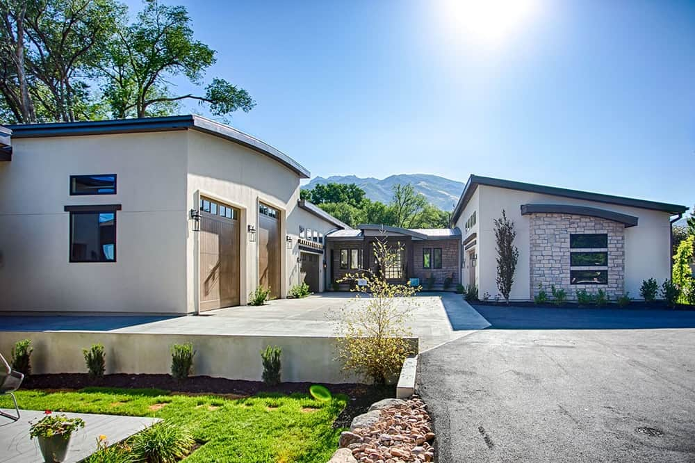 The front of the house has a garden lawn with a sitting area beside the elevated concrete driveway leading to the garage doors and the main entry of the house.