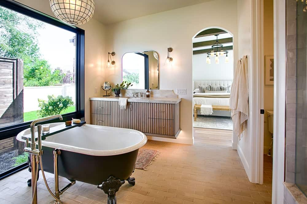 Ambient lighting from the round pendant and glass sconces bring a warm and cozy feel to this bright primary bathroom.