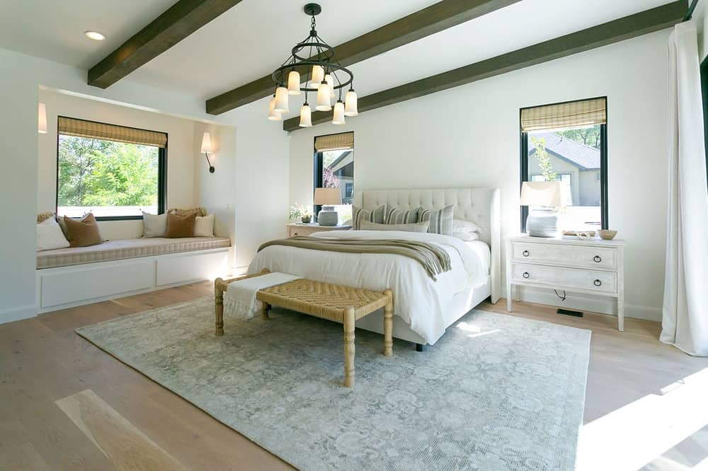 This primary bedroom highlights the cozy window seat nook and a shed ceiling lined with dark wood beams.