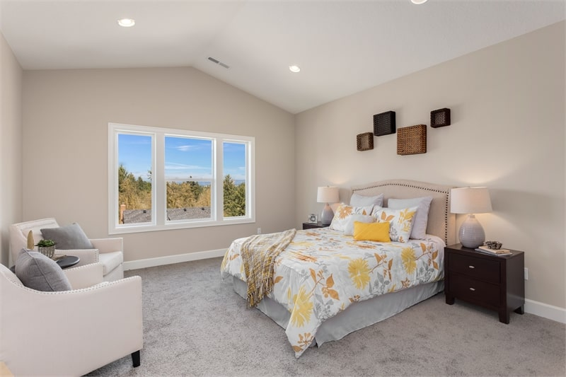 The primary bedroom has a cozy bed with patterned sheets, cushioned armchairs, and framed artworks adorning the beige walls.