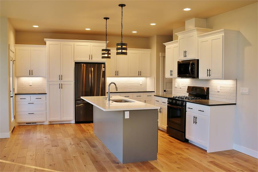 The kitchen has hardwood flooring that complements the beige cabinetry contrasted by the dark appliances and gray kitchen island topped with pendant lights.