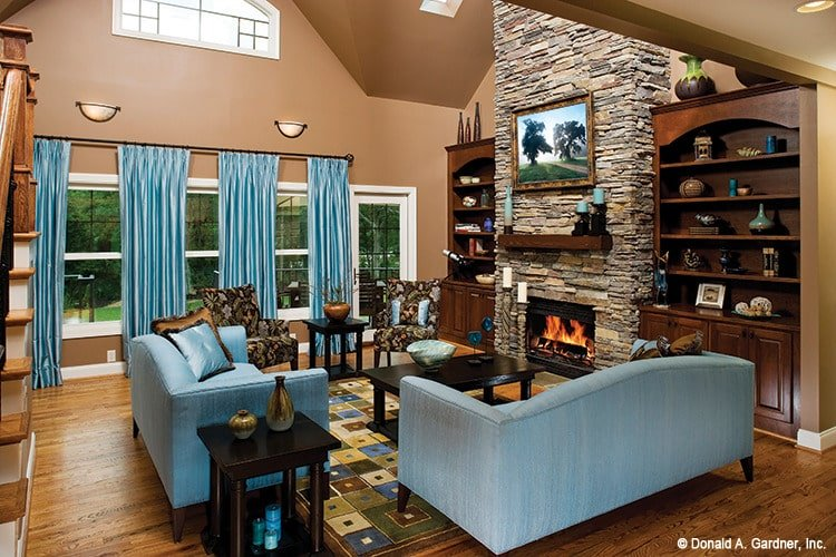 Matching blue sofas and draperies complements well with the brown walls and wooden furnishings of this living room.