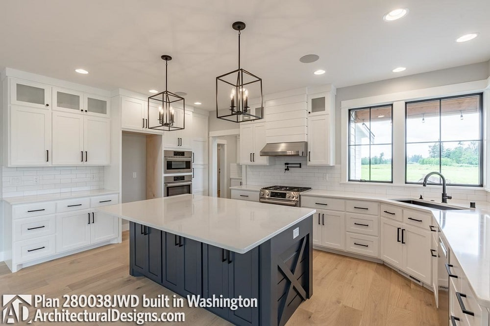 The kitchen has a large kitchen island that has a beige countertop to match the surrounding cabinetry along the walls. This is then contrasted by the dark gray island and the wrought-iron pendant lights above.