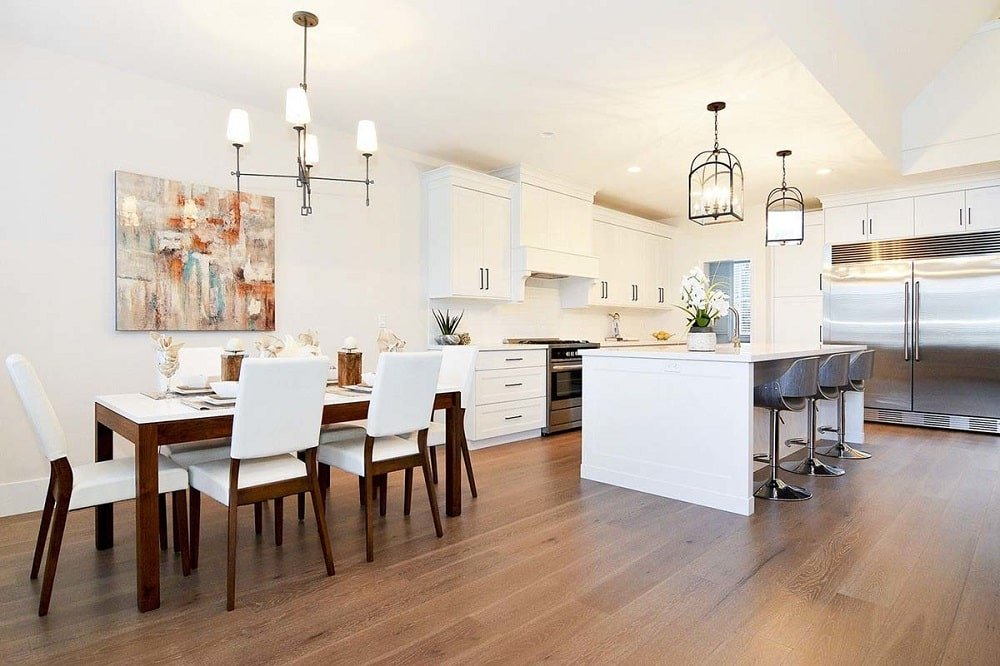 The eat-in kitchen has a large white kitchen island paired with stools and topped with a couple of lantern pendant lights. This also matches the simple chandelier above the dining set.