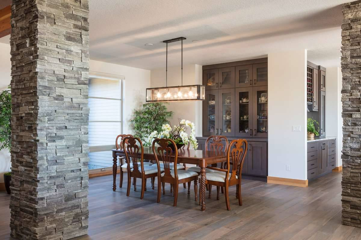 A formal dining room defined by large stone pillars. It has a wooden dining set, a linear chandelier, and a built-in china cabinet fitted against the inset wall.