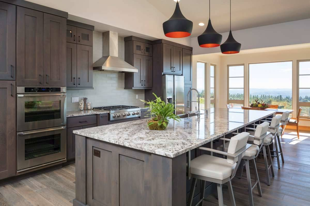 This kitchen features a granite top island complemented with cushioned chairs and eye-catching pendants. It includes natural wood cabinetry that blends in with the hardwood flooring.
