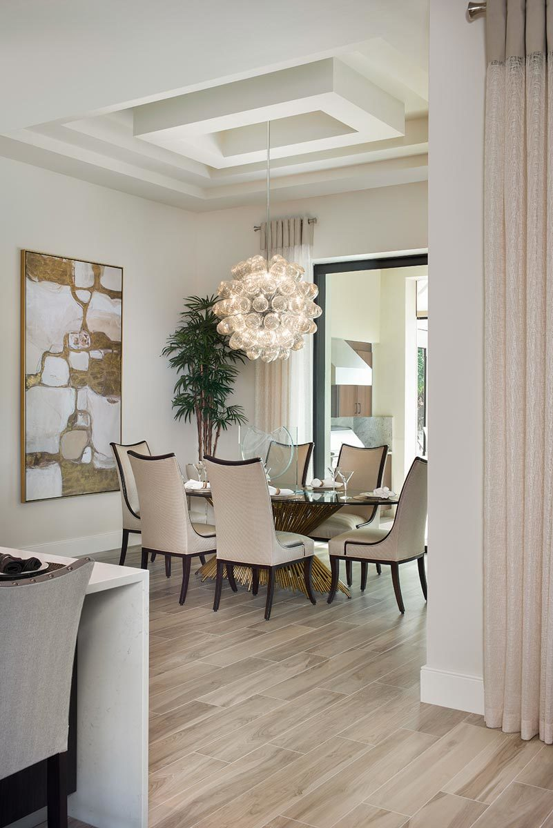 Dining room decorated with a stylish step ceiling, an oversized glass pendant, and a large artwork mounted against the beige wall.
