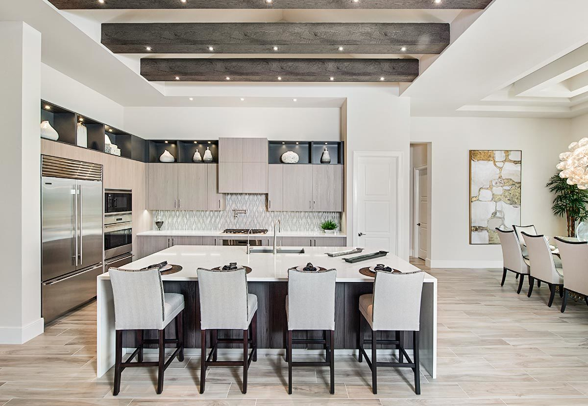 This kitchen showcases a neutral palette making the space appear brighter and bigger. Large wood beams on the tray ceiling soften the modern look.