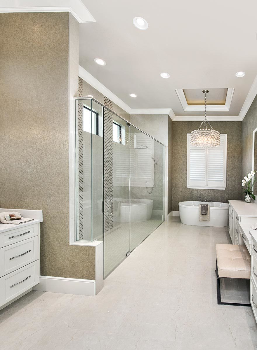 This primary bathroom offers an elongated walk-in shower, multiple vanities, and a freestanding tub illuminated by a fancy drum chandelier.