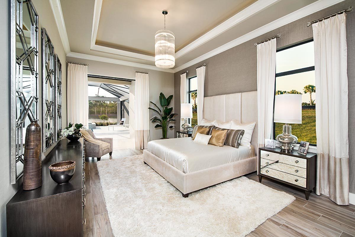 This primary bedroom features a decorative tray ceiling and light hardwood flooring topped by a shaggy area rug. Large windows and sliding doors invite natural light in.