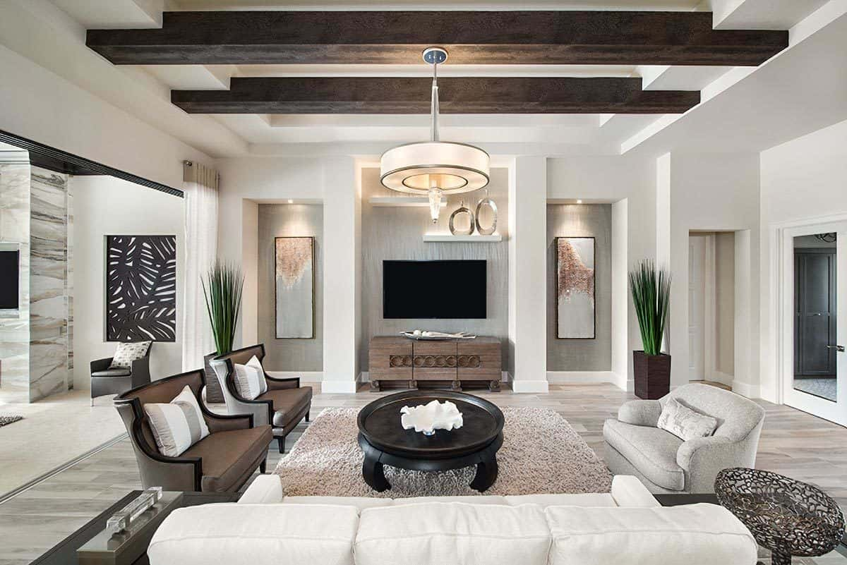 Contemporary living room with inset niche walls and a stunning tray ceiling lined with dark wood beams. Ambient lighting sets a cozy ambiance to the room.