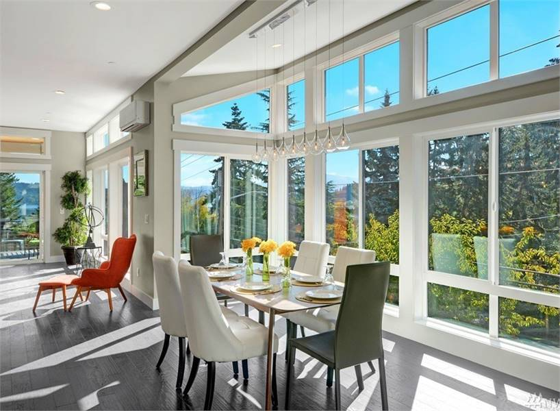 Contemporary dining room with a rectangular dining table and mismatched chairs. Floor-to-ceiling windows flood the room with natural light.