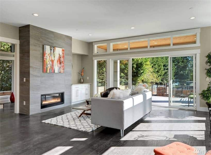 Contemporary living room with a sleek fireplace and a gray sofa supported by glass legs. It includes oversized sliding doors that extend the living space onto a spacious deck.