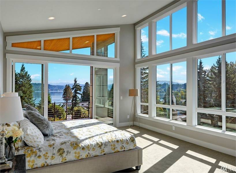 Floor-to-ceiling windows give this primary bedroom an incredible panoramic view. It has carpet flooring and oversized sliding doors that take you to its private deck.