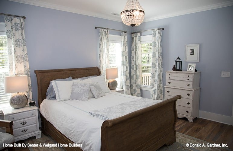 The primary bedroom has a large dark wooden sleigh bed topped with a crystal chandelier and flanked by white bedside drawers to match the dresser.