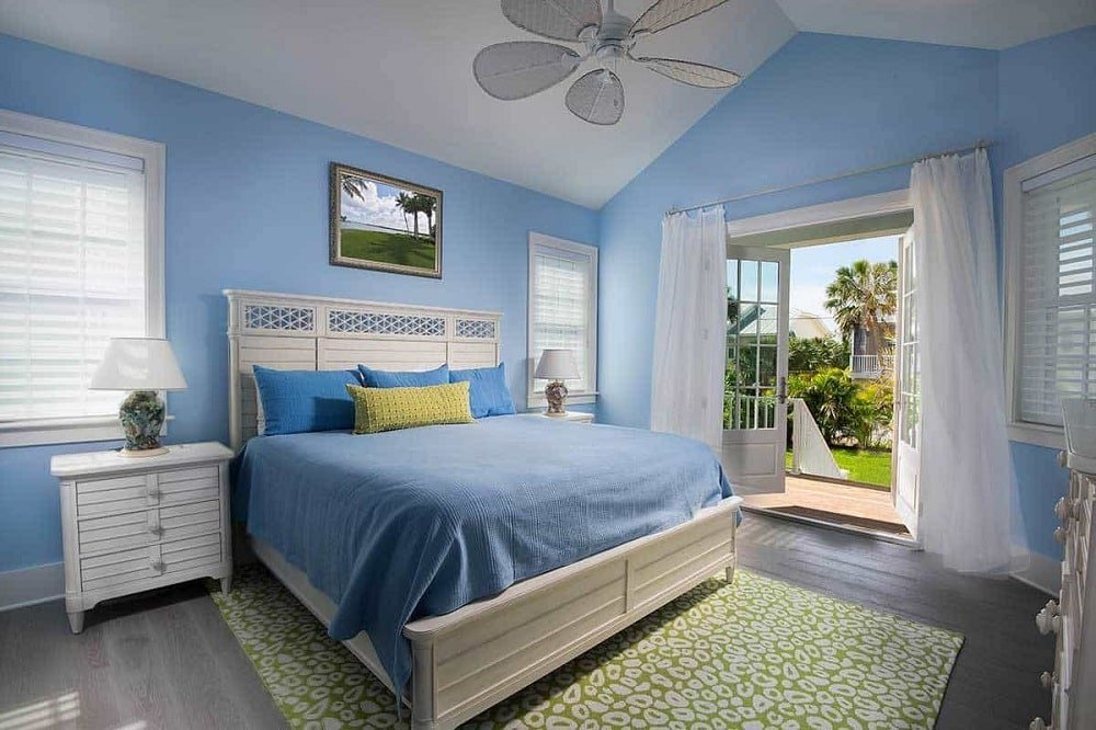 The primary bedroom has a white wooden bed frame and a balcony, cathedral ceiling, and blue walls that match the beddings.