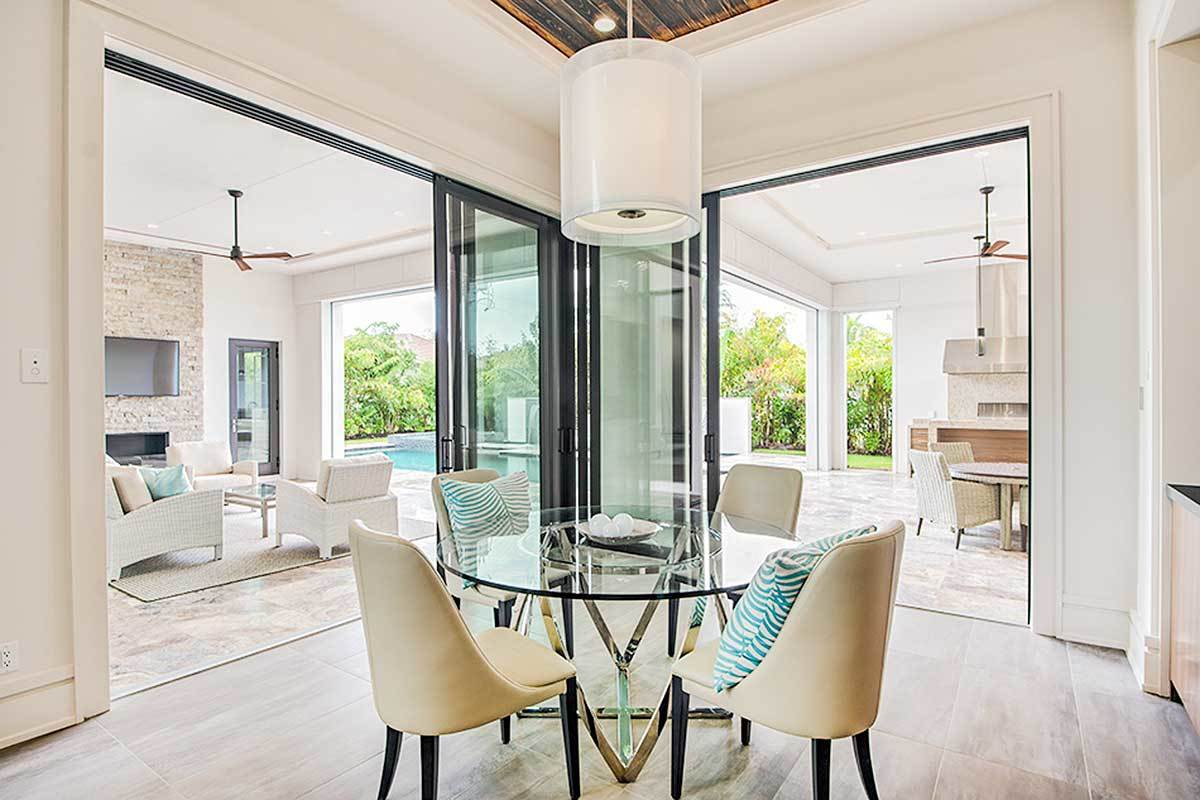 Oversized sliding doors on two sides extend this dining area outdoors. It has a round dining set topped with a cylindrical pendant.