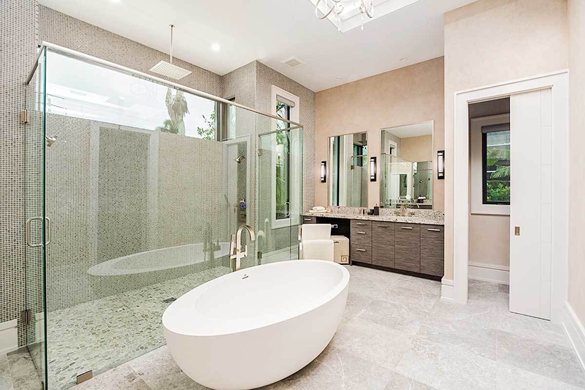Contemporary bathroom equipped with a wooden vanity, a deep soaking tub, and a spacious walk-in shower accentuated with mosaic tile backsplash.