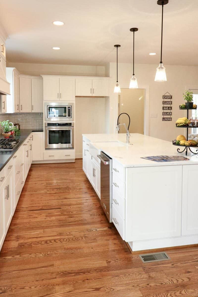 The kitchen features rich hardwood flooring, white cabinetry, and tiled backsplash beautifully contrasted with the black granite countertop.