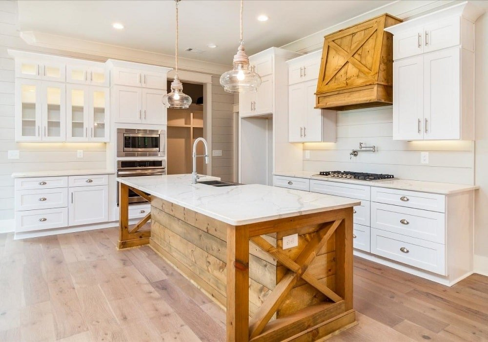 This is a close look at the Farmhouse-style kitchen with a kitche island that blends with the hardwood flooring and the vent hood above the cooking area. These are then complemented by the white cabinetry and white countertops.