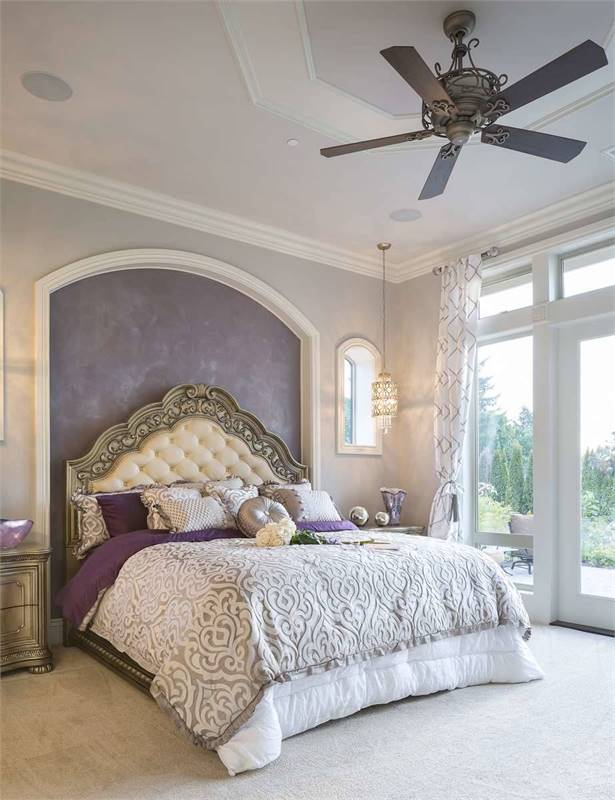 This is the primary bedroom with a ceiling fan and an elegant tufted bed situated on the arched inset wall with a purple tone to match the sheet of the bed that is bathed with natural lights from the glass doors.