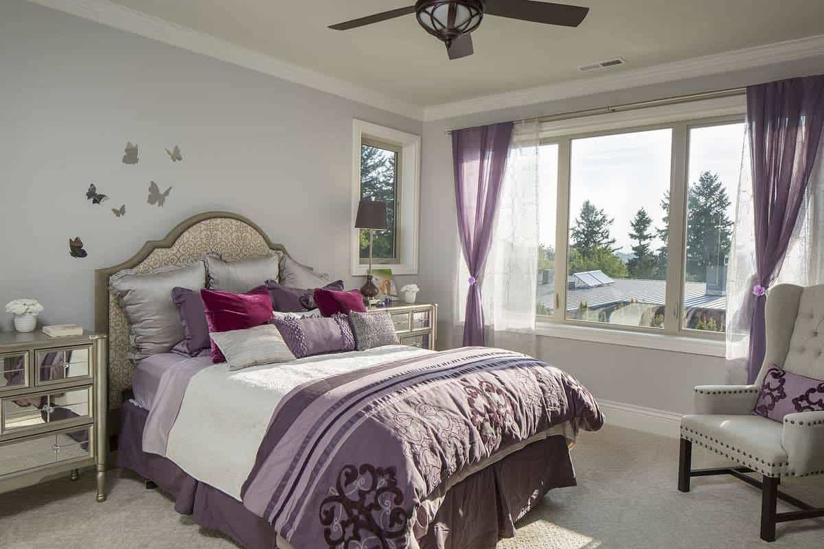This bedroom is filled with a gray wingback chair and a skirted bed flanked by mirrored nightstands. The chic purple sheets of the bed matches well with the curtains of the wide glass windows.