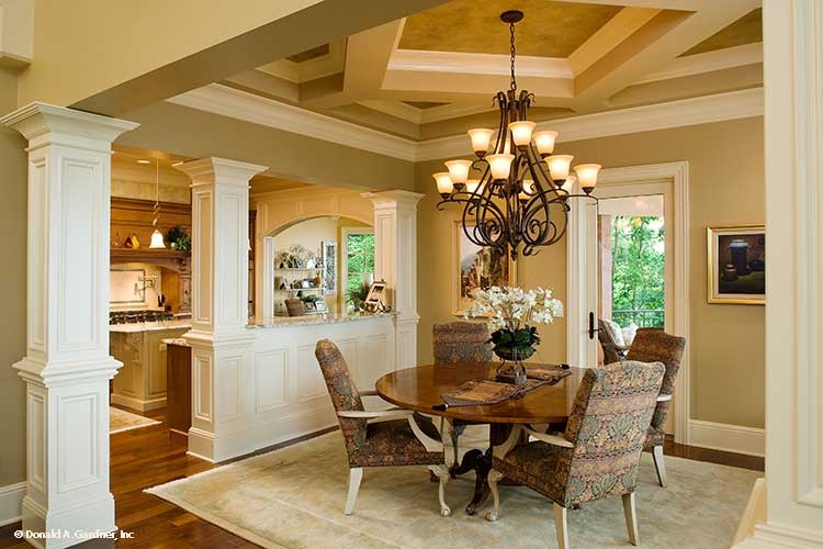 Dining area with patterned upholstered chairs, a round dining table, and an ornate chandelier that hangs from the decorative tray ceiling that matches the walls and white dividers.