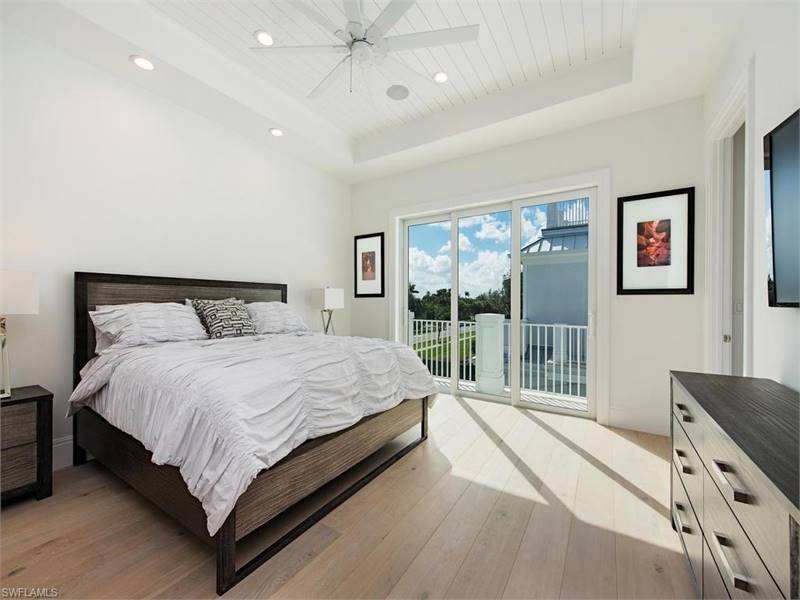 The primary bedroom has simple beige walls and tray ceiling with a ceiling fan over the large bed that matches the hardwood flooring.