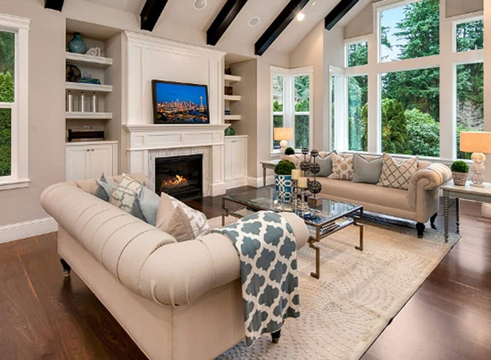 This living room has a couple of beige comfortable sofas on each side of the glass-top coffee table across from the fireplace that has a white mantle. This matches well with the white cathedral ceiling that has exposed dark wooden beams.