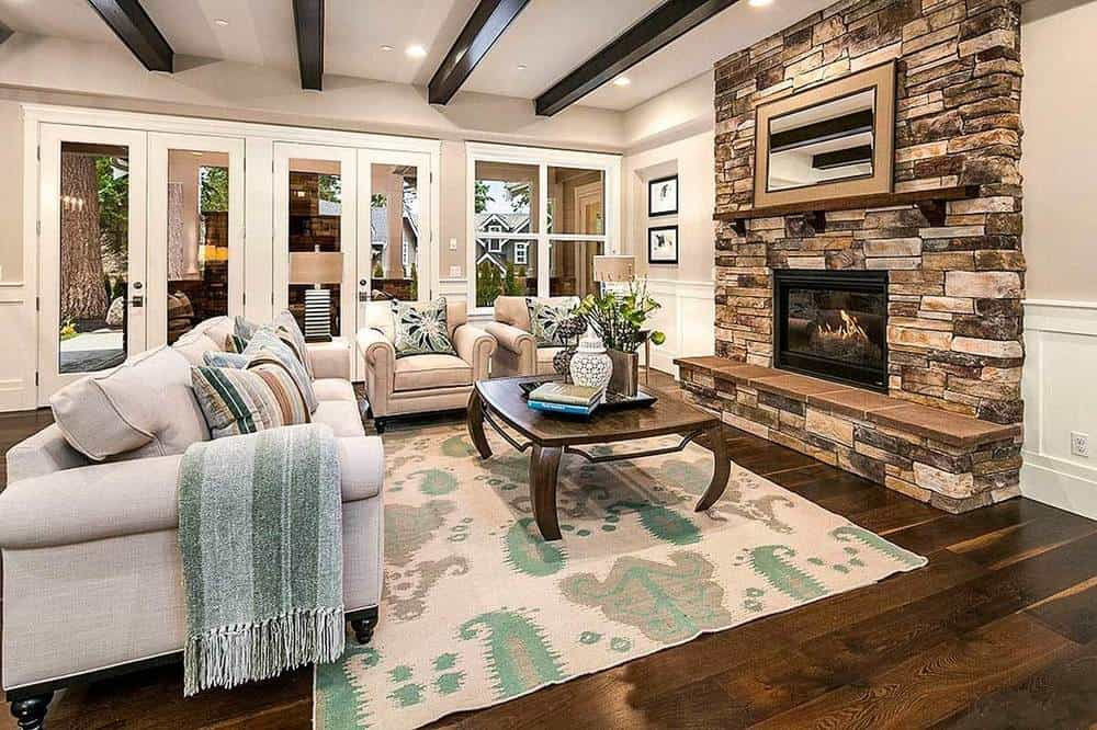This living room has exposed wooden beams on its beige ceiling to pair with the dark hardwood flooring that is covered with a colorful patterned area rug that pairs well with the pillows and sheets of the sofa set facing the fireplace.