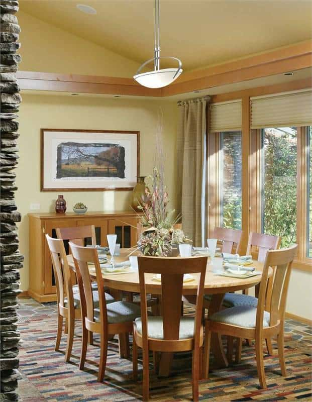 This is a charming dining room just beside the foyer. It has an elliptical wooden dining table paired with matching wooden chairs surrounded by beige walls and arched ceiling illuminated by the natural lights of the glass windows.