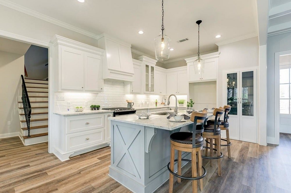 This is a bright beige Farmhouse-style kitchen with a light gray kitchen island surrounded by beige cabinetry that blends well with the walls and ceiling complemented by the hardwood flooring and stools.