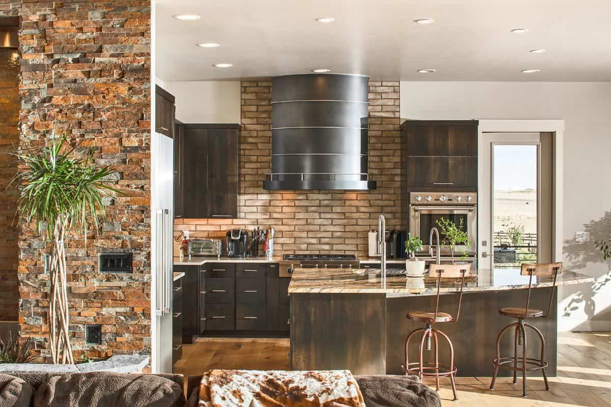A brick backsplash adds a striking texture to this contemporary kitchen. It includes dark wood cabinetry and a large multi-use island paired with metal counter chairs.