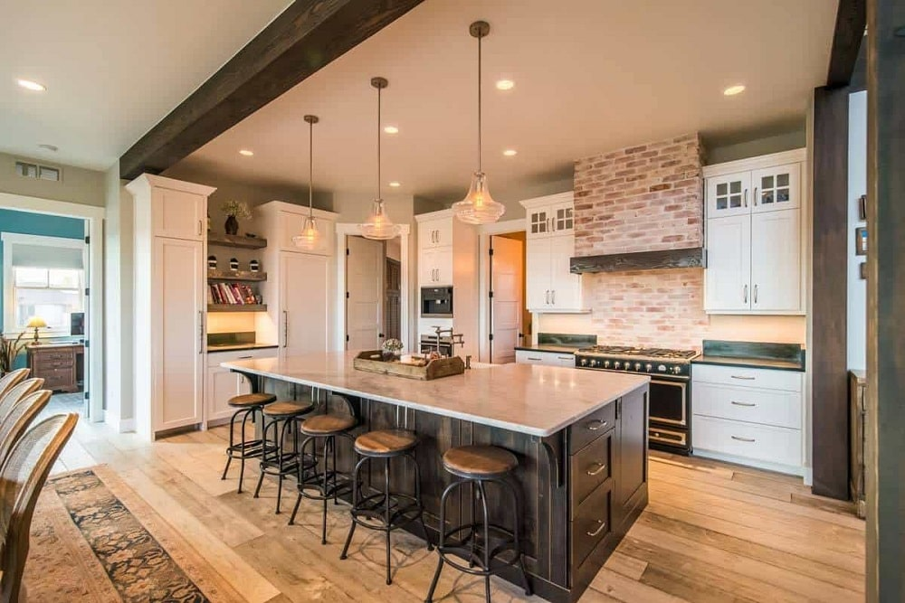 This is a close look at the kitchen that has a large kitchen island with dark cabinetry contrasted by the white countertop topped with pendant lights and paired with stools.